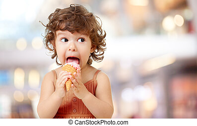 Kid eating ice cream in cafe. Funy curly child with icecream...
