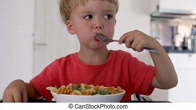 Kid eating macaroni - The child in the kitchen at the table...