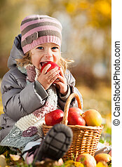 Kid eating red apple - Happy kid eating red apple in autumn ...