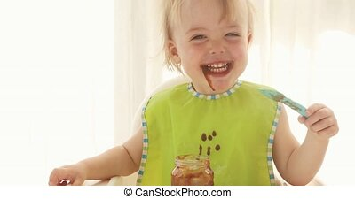 Kid eats puree from prunes and gets dirty - A baby grabbing...