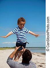 Kid Enjoying as His Dad Lifts Him - Dad lifting his young ...