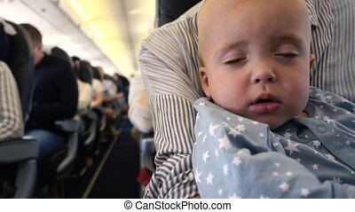Kid falls asleep in the plane at mom's hands