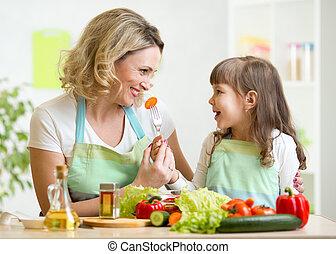 kid feeding mother vegetables in kitchen