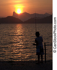 Kid fishing on the sunset in Rio de Janeiro