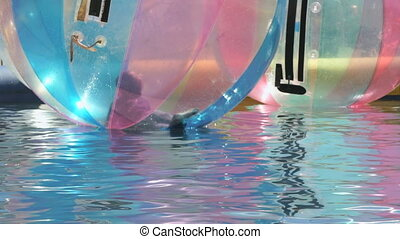 Kid flounders inside big inflatable ball in a pool
