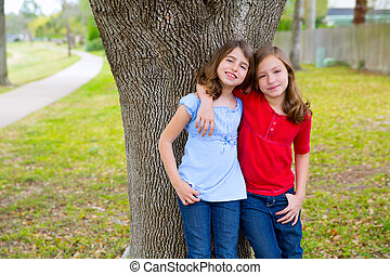 kid friend girls whispering ear playing in a park tree