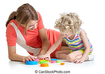 kid girl and her mom play together with cup toys