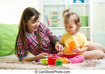 kid girl and her mother playing together at home