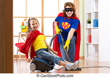 Kid girl and her mother weared Superhero costumes. Cute helper child and woman make cleaning room and have a fun.
