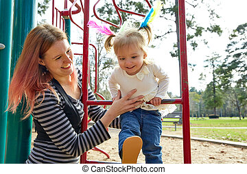 Kid girl and mother playing playground ladder