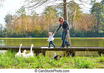 Kid girl and mother playing with ducks in lake - Kid girl ...