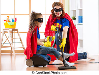 Kid girl and mother weared Superhero costumes. Cute helper child and woman make cleaning room and have a fun.