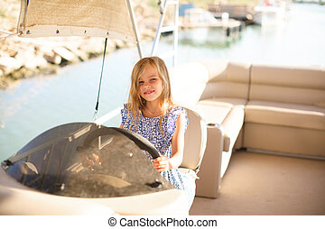 kid girl at helm of boat on pier. travel on water.
