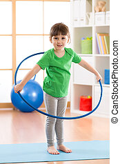 kid girl doing gymnastic with hoop in children room at home