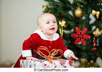 kid girl dressed as Santa Claus in front of Christmas tree with gift