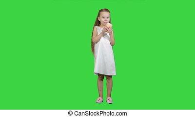Kid girl eating ice cream on a Green Screen, Chroma Key....