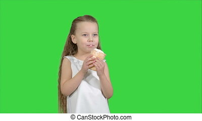 Kid girl eating with ice cream on a Green Screen, Chroma Key