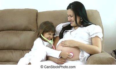 kid girl examining pregnant mother's tummy