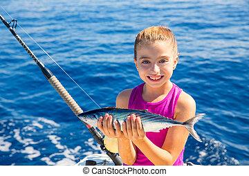 kid girl fishing tuna bonito sarda fish happy with trolling catch on boat deck