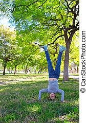 girl handstands upside down in the park