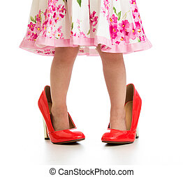 Kid girl in big red shoes isolated on white