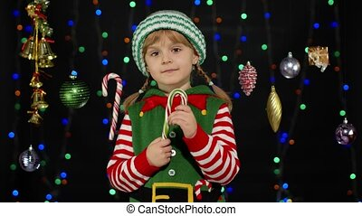 Blonde kid girl in Christmas elf Santa Claus helper costume licking candy cane lollipop isolated on black background with garland. Child enjoying caramel sweets. People New Year holidays celebration