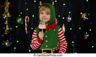 Blonde kid girl in Christmas elf Santa Claus helper costume licking candy lollipop sweets isolated on black background with garland. Child enjoying caramel sweets. People New Year holidays celebration