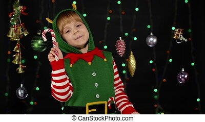 Happy kid girl in Christmas elf Santa Claus helper costume with candy cane lollipop on background with garland, decorations. Child joyful smiling, showing tongue. People New Year holidays celebration