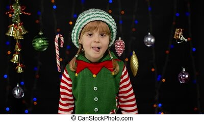 Kid teen girl in Christmas elf Santa helper costume. Child looking around for gift and receiving present lollipop candy cane, expressing amazement, extreme happiness. New Year holidays celebration