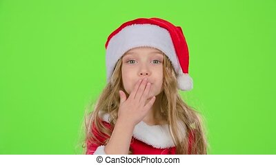 Kid girl in red Christmas caps send air kisses. Green screen