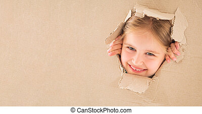 Kid girl looking through hole in the box