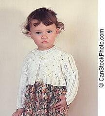 Kid girl model posing in fashion beautiful dress with serious face