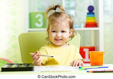 Kid girl painting with watercolors at home or preschool nursery