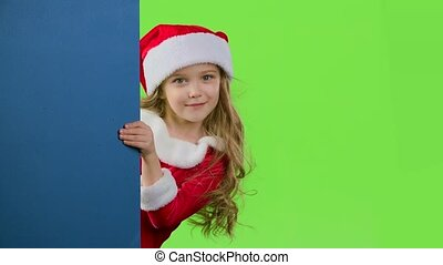 Kid girl peeking out from behind the blue board. Green...