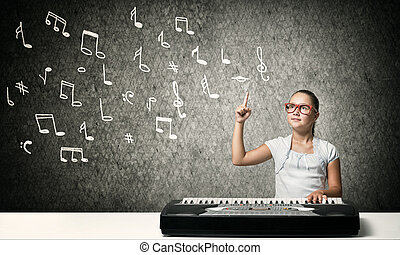 Kid girl play synthesizer - Cute school girl in red glasses...