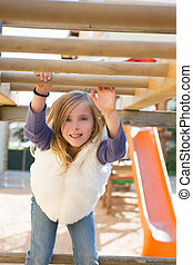 kid girl playing in playground  hanging from wood bars