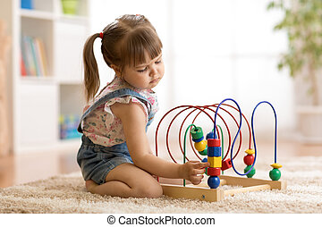 kid girl plays with educational toy indoors