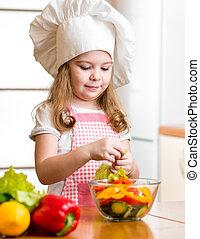 kid girl preparing healthy food vegetable salad