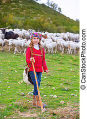 Kid girl shepherdess happy with flock of sheep and stick -...