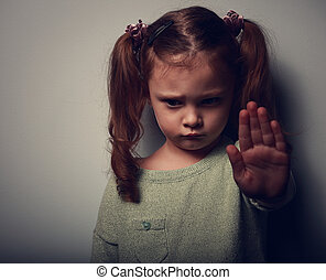 Kid girl showing hand signaling to stop violence and looking...