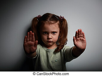 Kid girl showing two hands signaling to stop violence and...