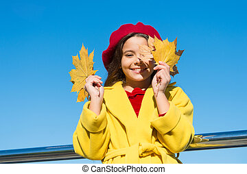 Kid girl smiling face hold leaves sky background. Child with autumn maple leaves walk. Autumn coziness is just around. Little girl excited about autumn season. Autumn warm season pleasant moments