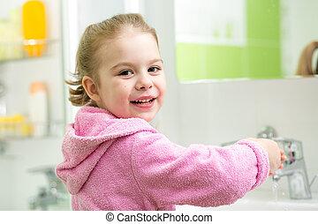 kid girl washing her hands in bathroom