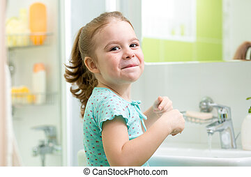 kid girl washing his face and hands in bathroom