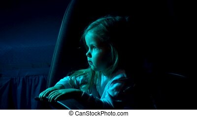 Kid girl watching TV movies or cartoons in dark room at home