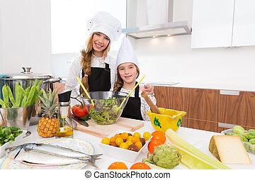 Kid girls junior chef friends hug together in countertop...