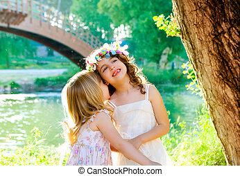 kid girls playing in spring outdoor river park whispering ear