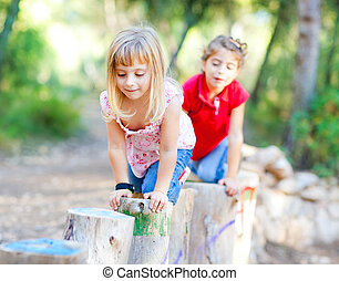kid girls playing on trunks in forest nature - kid girls...