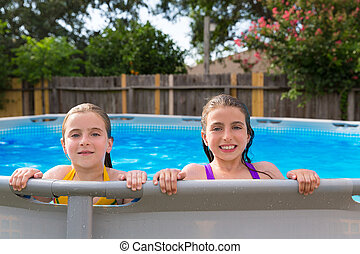 kid girls swimming in the pool in backyard