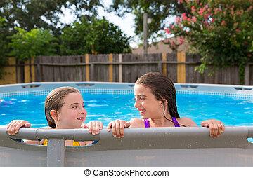 kid girls swimming in the pool in backyard